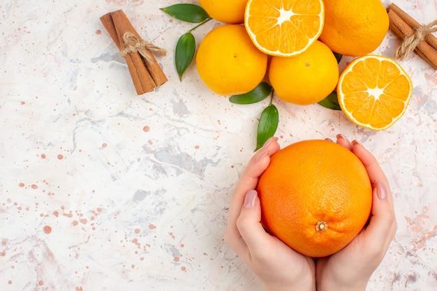 Vista superior tangerinas frescas em paus de canela cortadas laranja nas mãos da mulher em local livre de superfície brilhante e isolado