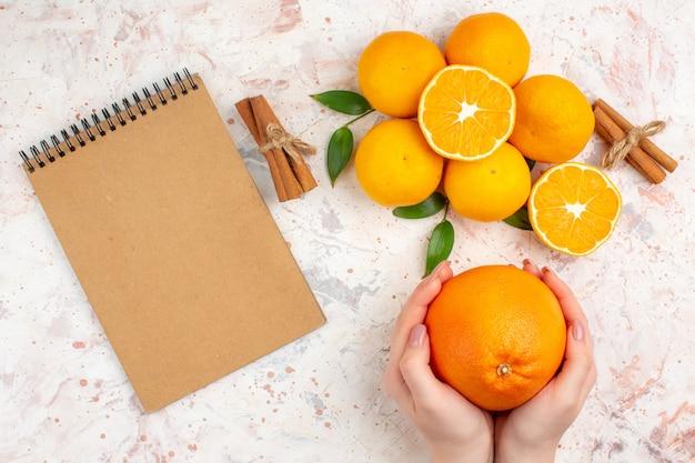 Vista superior tangerinas frescas em paus de canela cortados em laranja. mulher entrega um caderno em uma superfície brilhante isolada