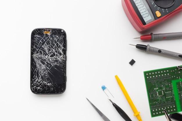 Vista superior telefone quebrado com ferramentas eletrônicas