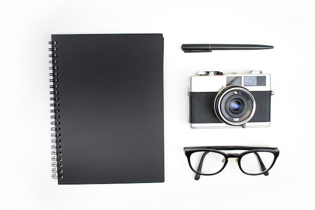 Vista superior, tema liso, preto de cadernos, caixas de filme, óculos e canetas de leitura isolados