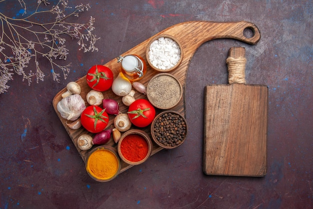 Vista superior temperos no quadro especiarias tomates cebolas cogumelos e uma garrafa de óleo e a tábua de corte