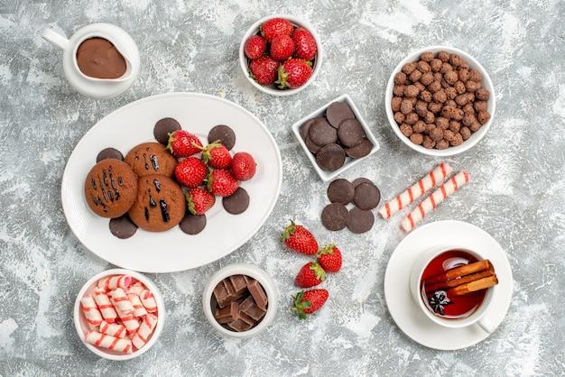 Vista superior tigelas com doces morangos chocolates cereais doces cacau e alguns morangos bombons chocolates e uma xícara de chá no fundo branco-acinzentado