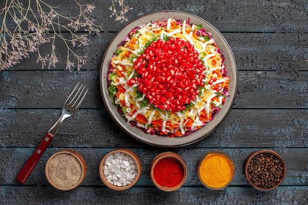 Vista superior tigelas de comida de natal com especiarias ao lado do garfo prato de natal com romã e maionese e galhos de árvores