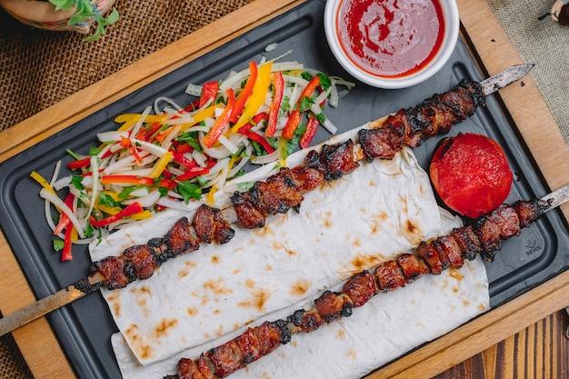 Vista superior tike kebab no espeto no pão pita com salada de legumes e ketchup