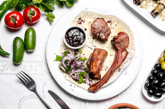 Vista superior tike kebab no pão pita com ervas e cebolas com molho e legumes