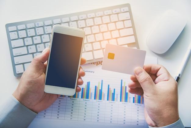 Vista superior titulares de cartão de crédito usado laptops e smartphone encomenda e pagamento