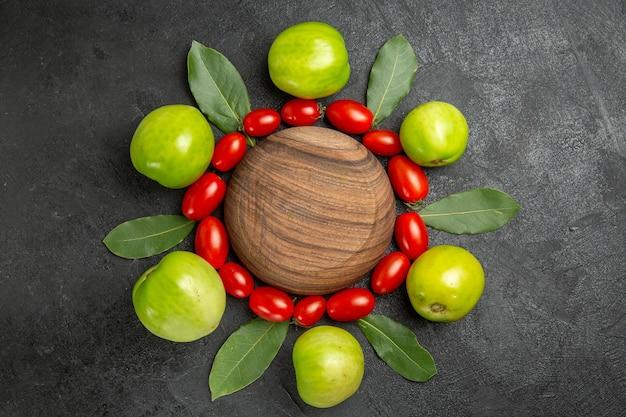 Vista superior tomate cereja tomate verde e folhas de louro em torno de uma placa de madeira em um solo escuro com espaço de cópia