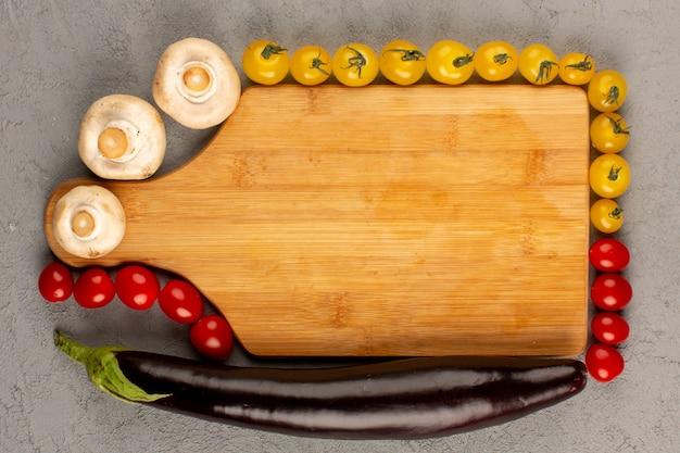 Vista superior tomate cogumelos berinjela fresca madura todo em torno da mesa marrom no chão cinza