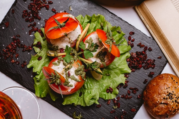 Vista superior tomate recheado com molho em uma folha de alface com fatias ‹limão e bérberis secas