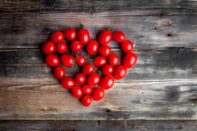 Vista superior tomates formando coração no fundo escuro de madeira. espaço horizontal para texto