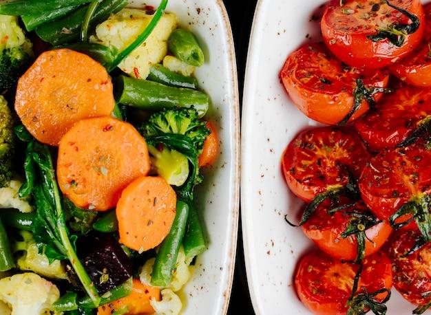 Vista superior tomates secos ao sol com legumes cozidos cenouras aspargos com brócolis