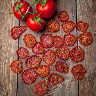Vista superior tomates secos e tomates frescos na mesa de madeira