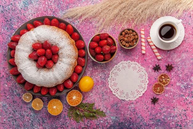 Vista superior torta de açúcar em pó e bolo de morango com uma xícara de chá rosa