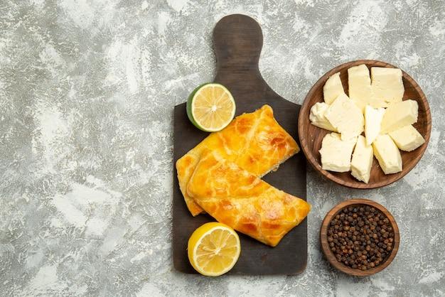 Vista superior tortas de queijo tigelas de tortas apetitosas de queijo de pimenta preta e limão na tábua de corte no lado direito da mesa