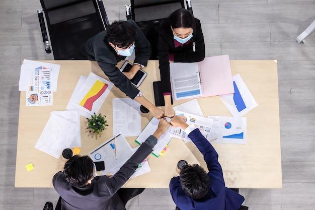 Vista superior trabalhadores de sucesso grupo de parceiros de negócios asiáticos usando máscara protetora casual com diversos gêneros (lgbt), colocando as mãos juntas na reunião na sala do escritório, covid-19