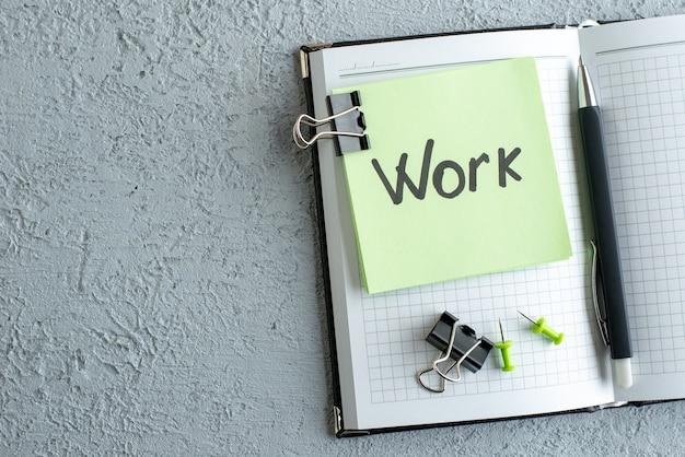 Vista superior trabalho nota escrita no adesivo verde com bloco de notas e caneta no fundo branco faculdade cor trabalho escola escritório foto caderno de negócios