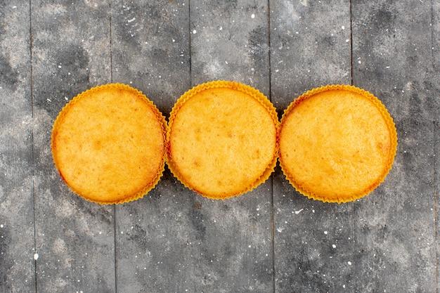 Vista superior três bolos marrom cozido redondo sobre o fundo cinza de madeira rústico