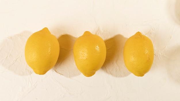 Vista superior três limões frescos alinhados na mesa