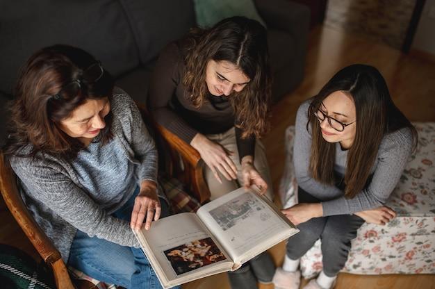 Vista superior três mulheres, mãe e filhas procurando um livro de memórias. união, conceito de família.
