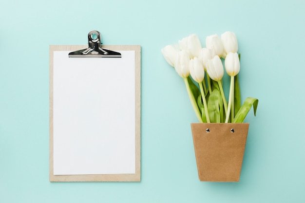 Vista superior tulipa branca flores e bloco de notas