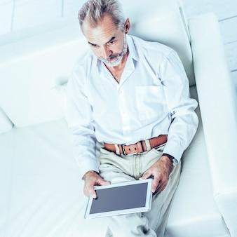 Vista superior - um empresário de sucesso com tablet digital sentado na cadeira de escritório moderna.
