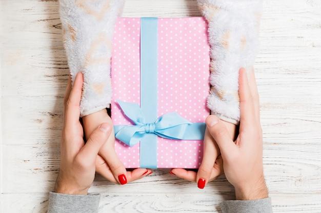 Vista superior, um homem e uma mulher dando e recebendo presentes para umas férias na madeira. fechar amor e relacionamento