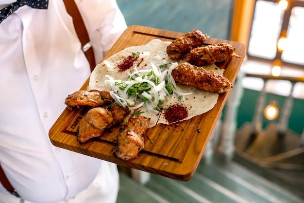Vista superior, um homem segura uma bandeja com lula e tike kebab em uma pita com cebola e ervas
