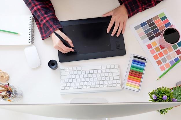 Vista superior um local de trabalho do artista com o designer gráfico que trabalha na mesa do espaço de trabalho.