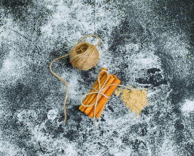 Vista superior uma bola de corda amarrada para secar a canela na superfície texturizada cinza. horizontal