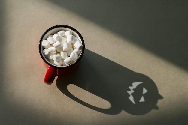 Vista superior, uma caneca de marshmallows e uma sombra assustadora com chifres e um rosto sinistro