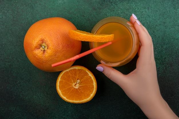 Vista superior, uma mulher segura na mão suco de laranja em um copo com canudo vermelho e uma fatia de laranja com toranja em um fundo verde