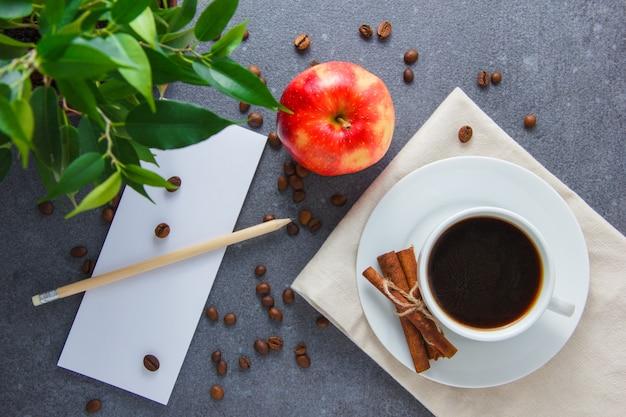 Vista superior, uma xícara de café com maçã, canela seca, planta, lápis e papel na superfície cinza. horizontal