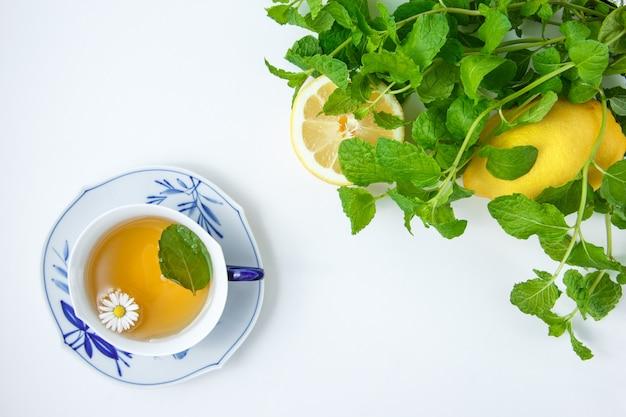 Vista superior uma xícara de camomila com limão, folhas de hortelã.