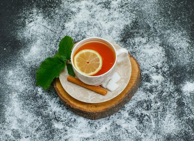 Vista superior uma xícara de chá com limão, canela seca, cubos de açúcar em fatias de madeira e escuro. horizontal