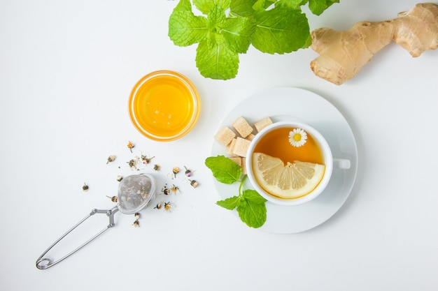Vista superior, uma xícara de chá de camomila com ervas, mel, folhas de hortelã, açúcar na superfície branca. horizontal