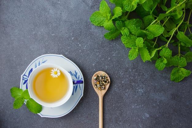 Vista superior uma xícara de chá de camomila com folhas de hortelã e ervas de camomila em colher.