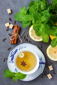 Vista superior uma xícara de chá de camomila com folhas de hortelã, limão, açúcar, canela seca.