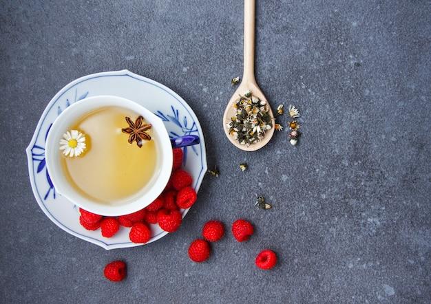 Vista superior uma xícara de chá de camomila com framboesa em um pires, ervas de camomila em colher.