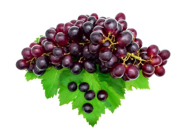 Vista superior uva vermelha madura com folhas isoladas em branco.