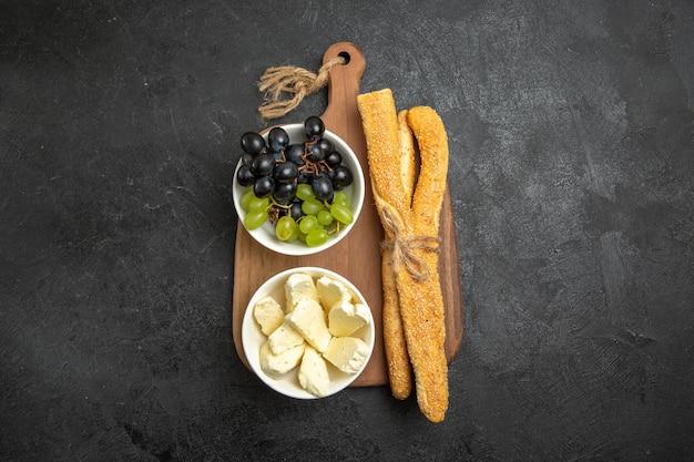 Vista superior uvas frescas com queijo e pão na superfície escura frutas maduras árvore madura vitamina alimentos leite