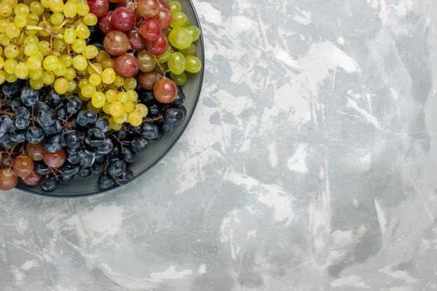 Vista superior uvas frescas frutas suculentas e maduras dentro do prato na mesa branca frutas suaves vinho fresco