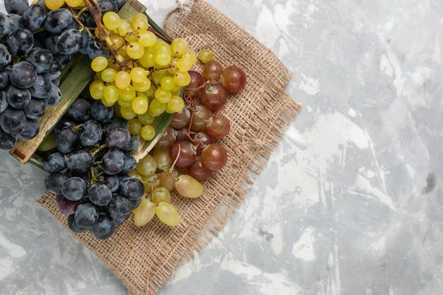 Vista superior uvas frescas frutas suculentas e maduras em fundo branco claro frutas maduras suculentas frescas