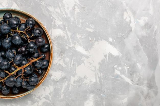 Vista superior uvas pretas frescas suculentas frutas suaves e doces na mesa branca clara