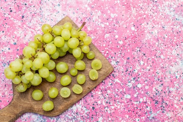 Vista superior uvas verdes frescas maduras e frutas suculentas na mesa brilhante