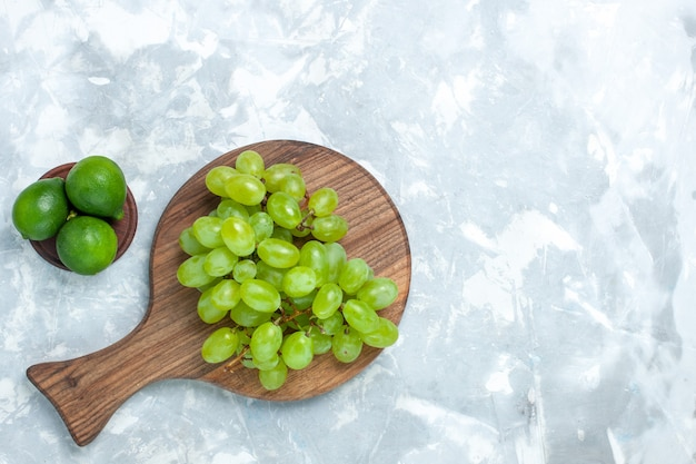 Vista superior uvas verdes frescas maduras frutas suculentas com limões na mesa de luz.