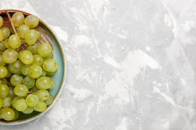 Vista superior uvas verdes frescas suculentas frutas suaves e doces na mesa branca