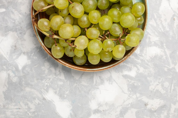 Vista superior uvas verdes frescas suculentas frutas suaves e doces na superfície branca