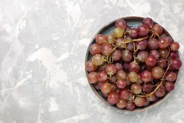 Vista superior uvas vermelhas frescas suculentas frutas suaves e doces na mesa branca