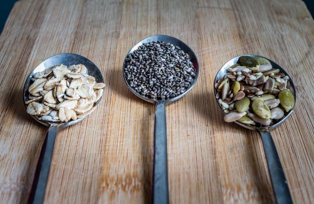 Vista superior, várias sementes em colheres na mesa de madeira