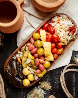 Vista superior variedade de pickles pepinos tomates repolho num prato